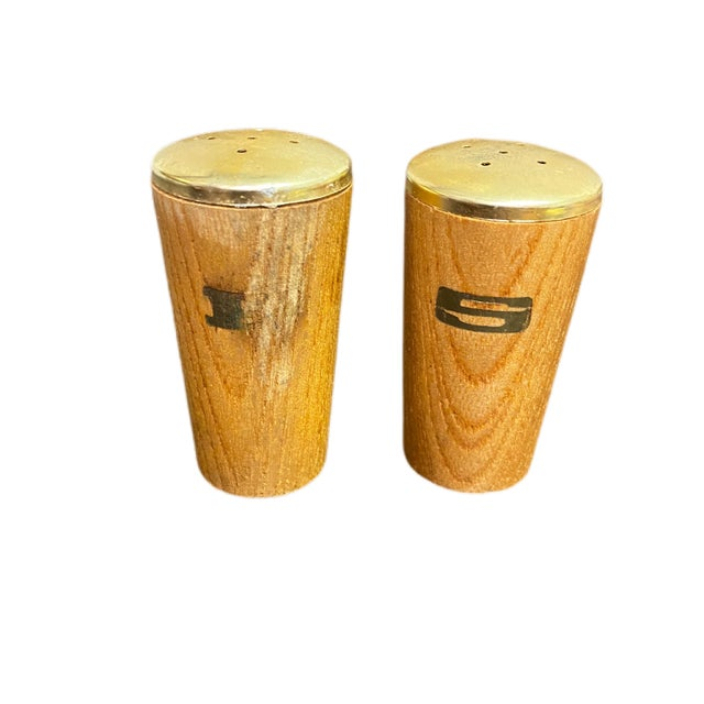 A lovely pair of teak and gold tone metal salt and pepper shakers. The P on the pepper shaker shows some wear.