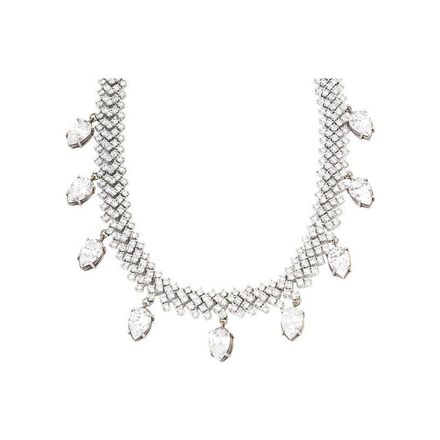 Flexible crystal necklace with nine dangling pear-shaped crystals mounted in white metal. No maker's mark. Minor wear, one...