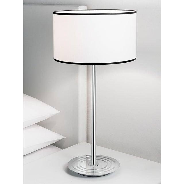 A retro style polished chrome table lamp with a base featuring detailed concentric grooves. There is a retro style white...