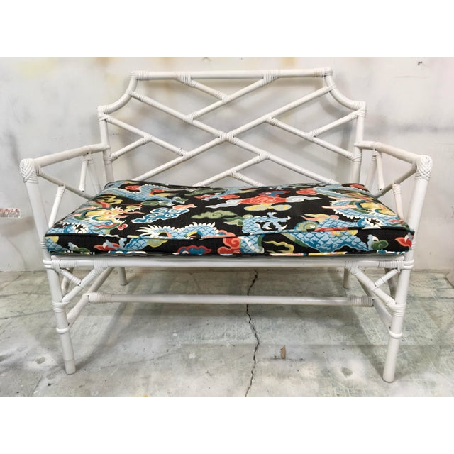 1960s Chinese Chippendale rattan settee with a new linen chinoiserie cushion. Age wear minor with some layers of paint....