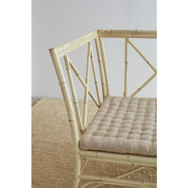 Elegant Hollywood Regency bamboo settee or bench featuring a cream colored lacquer finish. Delicate frame constructed from...