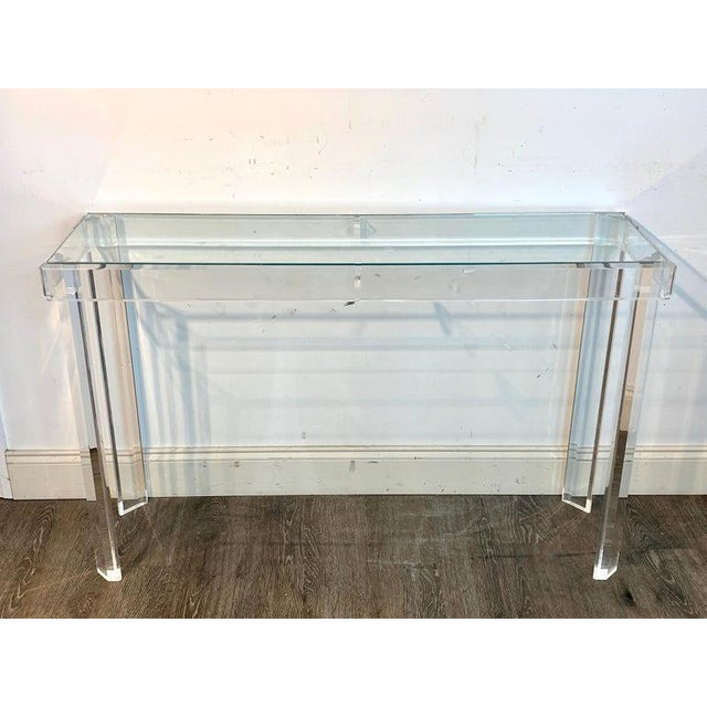 Sleek modern Lucite and glass console, with inset clear glass top, raised on four Marlbourgh legs.