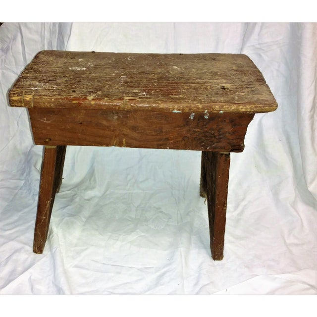 A carved painted cricket stool circa early 1900's with some residue of dry red paint. Hand carved with scars and saw cuts...