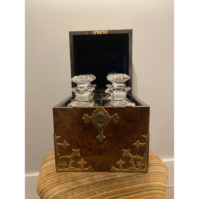 This is a beautiful English Burled Walnut Tantalus. It is antique and has four decanters with tops. Additionally there are...