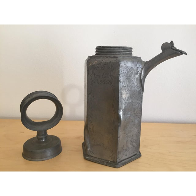 Antique, one-of-a-kind, hand-etched metal decanter; with a hoop handle that screws closed, and an articulated, lidded...
