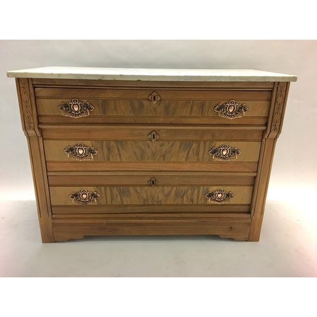 Late 1800's mahogany chest of drawers with a carerra marble top and copper hardware. Newly stripped to its natural wood....