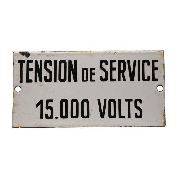 White and black enamel French sign saying Operating Voltage 15,000 volts.