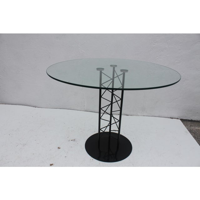 Stylish mid-century modern round dining table having a sculptural pedestal of Zig -Zagging black painted metal rods with...