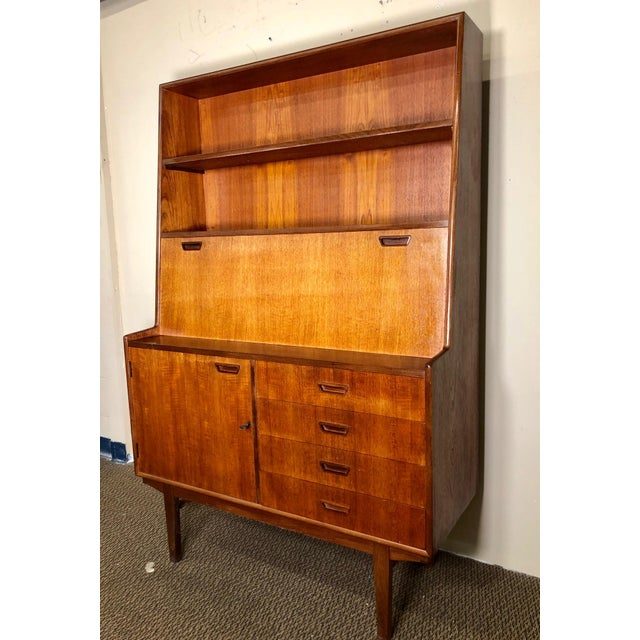 This is a beautiful teak secretary with 4 drawers and a cabinet door with key. Made by Turnidge of London. Original label...