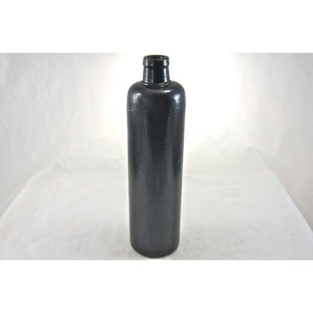Tall heavy rustic black glazed stoneware beverage bottle. No maker's mark. Light wear.