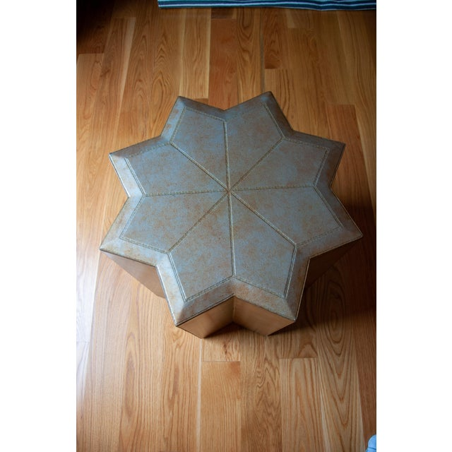 A unique and decorative leather covered, eight side star side table. The surface shows exposed stitching which adds a...
