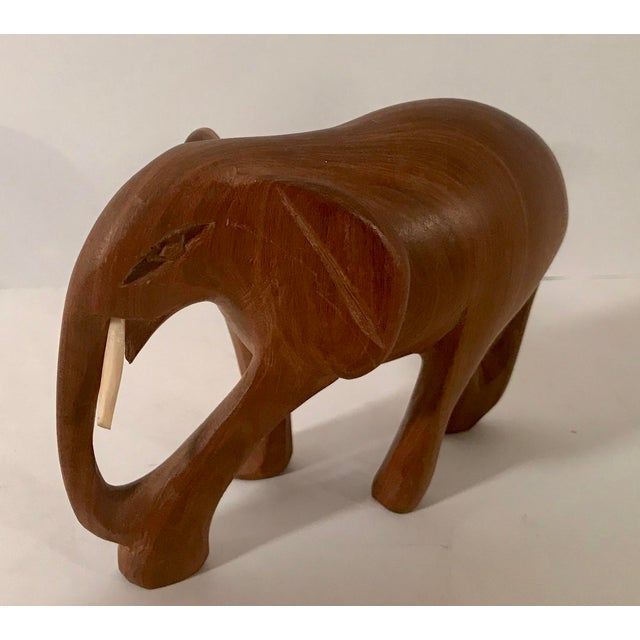 Wooden carved elephant with white tusks, probably bone. Nice vintage piece!