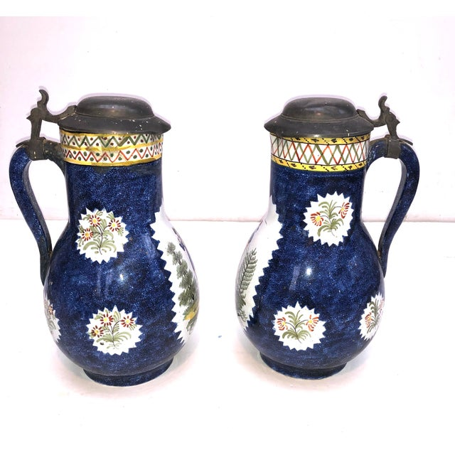 Lovely pair of Faience likely Brussels ceramic pewter lidded jugs. Hand painted/transferware depictions of a country...
