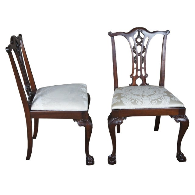 Two antique chippendale style side chairs. Made from mahogany with verticle slat back and ribbon design. Features cabriole...