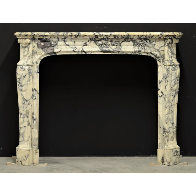Superb French Pompadour style Louis XV fireplace mantel executed in beautiful Paonazetto marble. The soft toned marble...