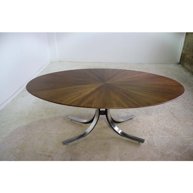 This beautiful Borsani dining table stands out, with its wood top featuring a starburst pattern within the wood grain....