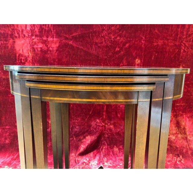 Rare mahogany three-tiered Weiman (Rockford, Illinois) nesting tables . Item features rolled edge, tooled and burnished...