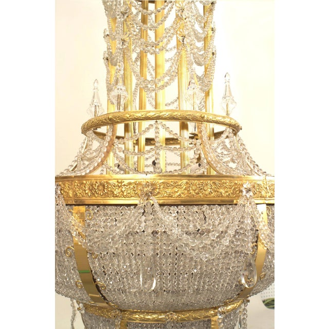 French Louis XVI style (circa 1900) gilt bronze and beaded crystal large chandelier with a dome form top and swag and...