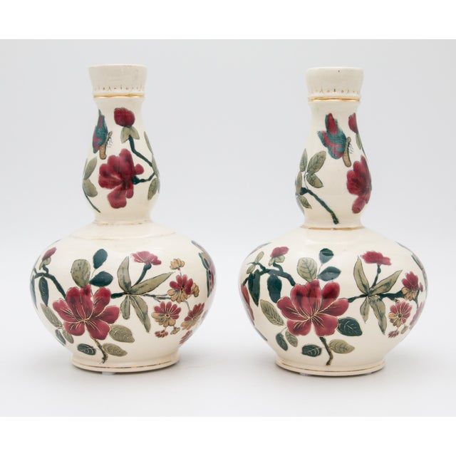 A gorgeous pair of early 20th-Century Italian faience double gourd vases. These lovely vases are hand painted with finely...