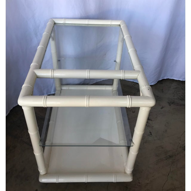 1980's White rattan design lacquer rolling bar cart. With (2) glass shelves. The top shelf is stationary and bottom...