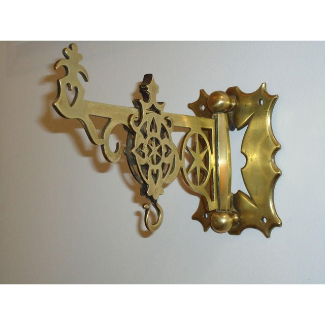 Early 19thC Brass wall bracket from New England. This fantastic folky wall hanger could be used to display leather fire...