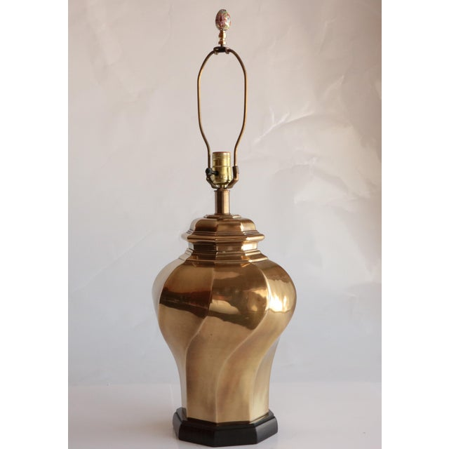 This brass lamp has a twisted urn shape and is topped with a dramatic Asian-style cloisonné finial. Original wiring in...