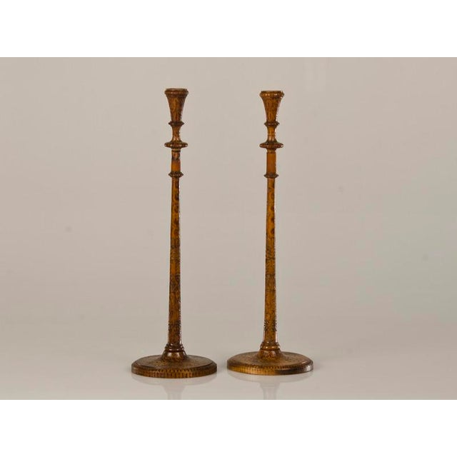 A pair of tall and slender candlesticks carved with poker work decoration from England c.1880. These elegant candlesticks...