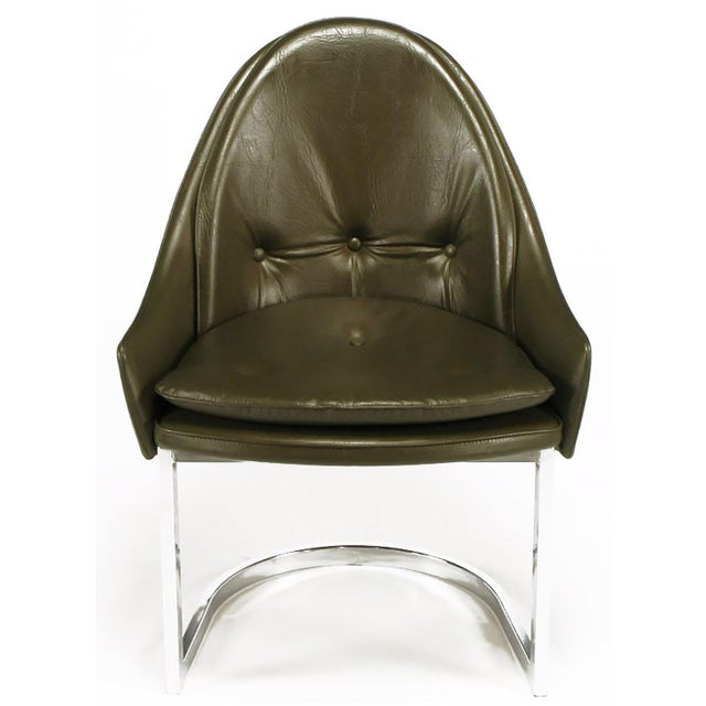Set of four chrome base dining chairs, in the manner of Harvey Probber. Dark chocolate vinyl upholstery. Fixed three-...