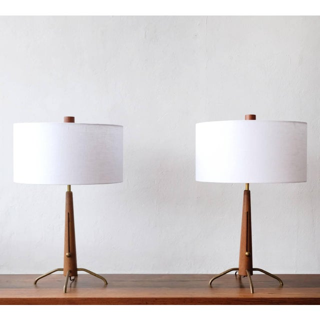 Pair of 1950s walnut and solid brass table lamps designed by Gerald Thurston for Lightolier. Solid brass balls unscrew to...