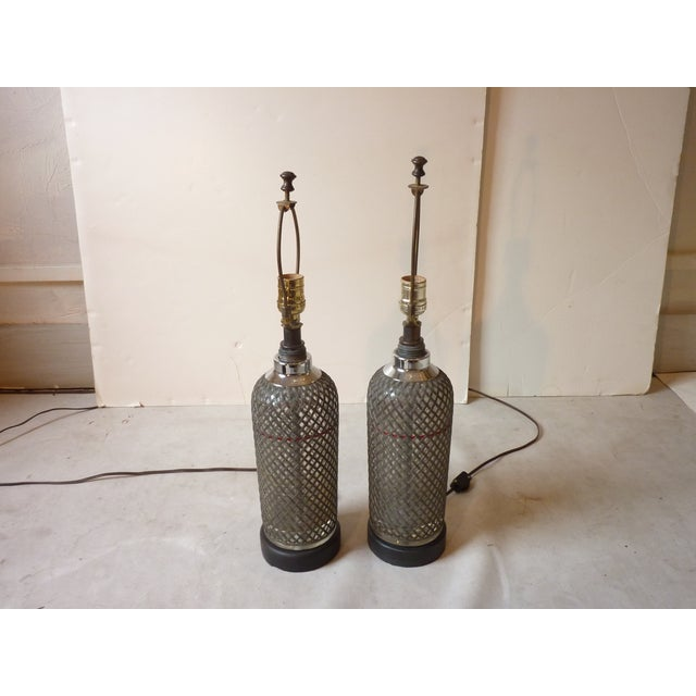 Pair of Art Deco Czecheslavakian selzer bottles, glass wrapped with metal wire, newly wired with black wooden bases priced...