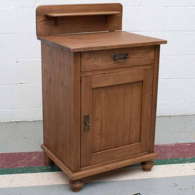 A small and versatile pine single door base, nightstand, or washstand with splashback gallery and shelf. One hand-cut...