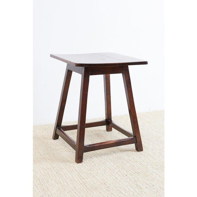 Handsome English oak tavern table or pub table. Featuring a plank top and canted or splayed legs. The legs are conjoined...
