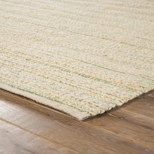 A natural area rug with a contemporary touch, this cotton-backed layer pops with a bleached white tone and hints of green...
