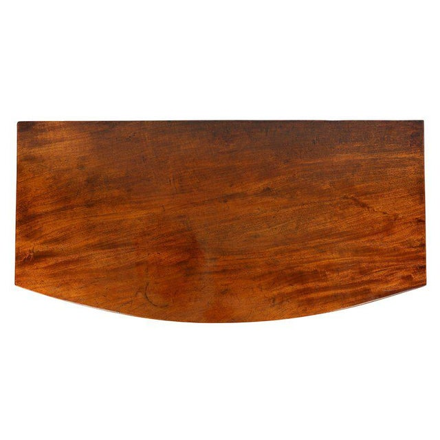 Rectangular solid mahogany top over two over three graduated drawers, splayed feet.