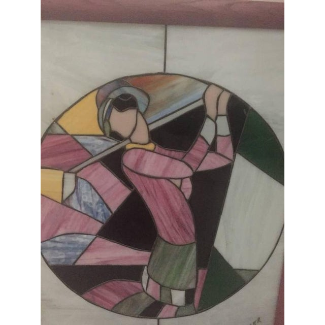 Art Deco stained glass of women playing golf signed by M Adler with pink wood frame.