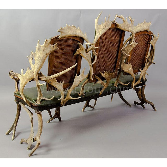 antler sofa with three seats, made of antlers from the deer and fallow deer. decorated with figural carved horn roses....