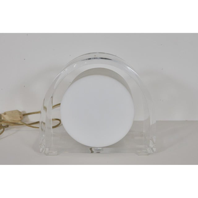 This exquisite demilune lucite lamp is made by the Ritts Company. The lamp has a milk lucite circular light fixture set in...