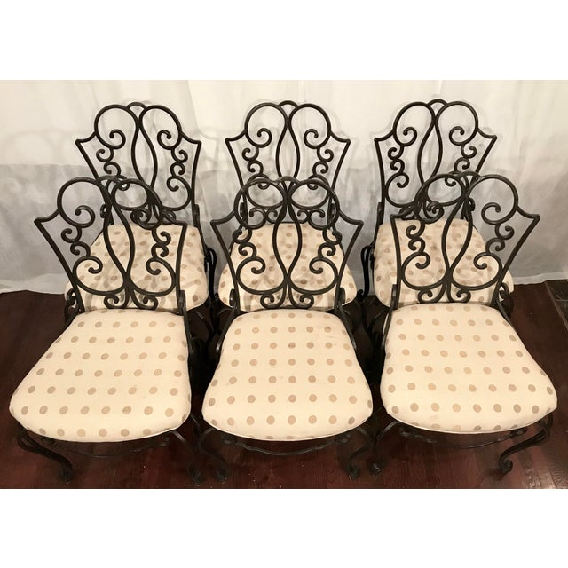 Beautiful scrolled, heavy French wrought iron chairs. These chairs are well padded and upholstered with a vanilla cream...