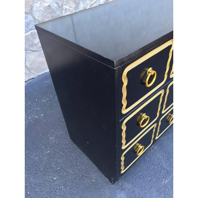 Black lacquered finish with three pull out drawers, gold trim and original gold pulls.