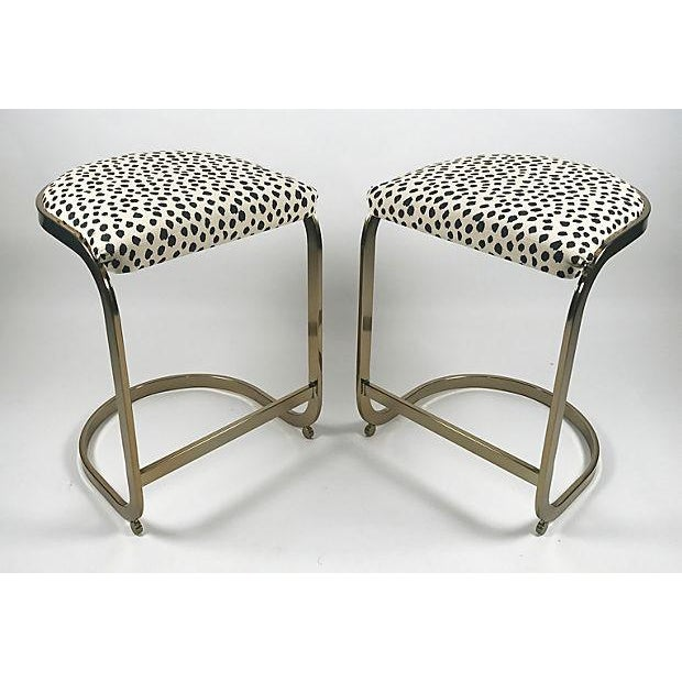 Pair of mid century Milo Baughman-style brass cantilevered stools. Newly upholstered in animal print cotton fabric.
