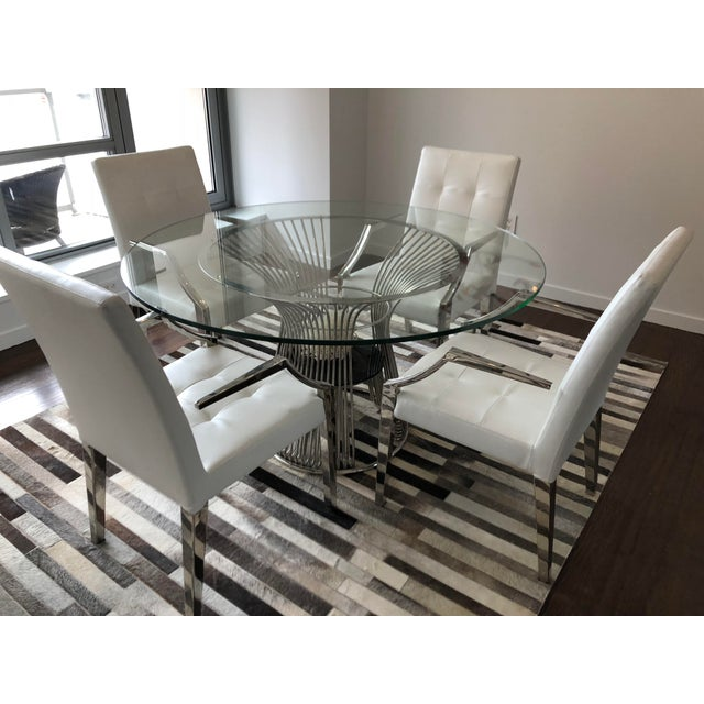 """4 white leather dining chairs and coordinating 54"""" diameter round glass dining table."""