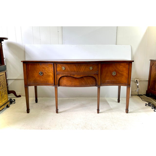 19th Century English sideboard, serpentine in shape and constructed of flame mahogany, made in the manner of George III. A...