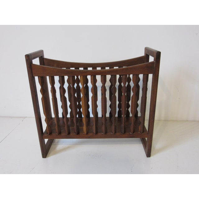 A solid walnut magazine rack with carved spindles manufactured by the Drexel furniture company and designed by Kipp Stewart.