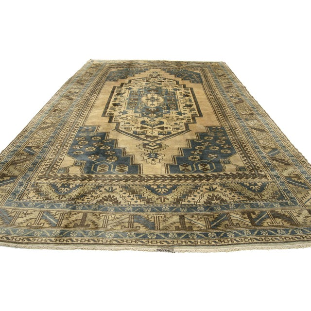 A vintage Turkish Oushak rug with medallion and corner design. This unique hand-knotted wool vintage Turkish Oushak rug...