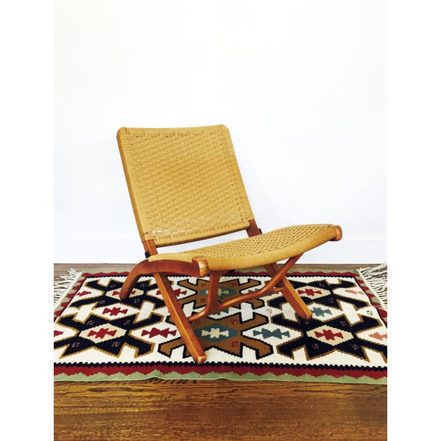 A Mid Century Hans Wegner Style folding rope lounge chair. The seat of the stool is made of woven jute and the wood frame...