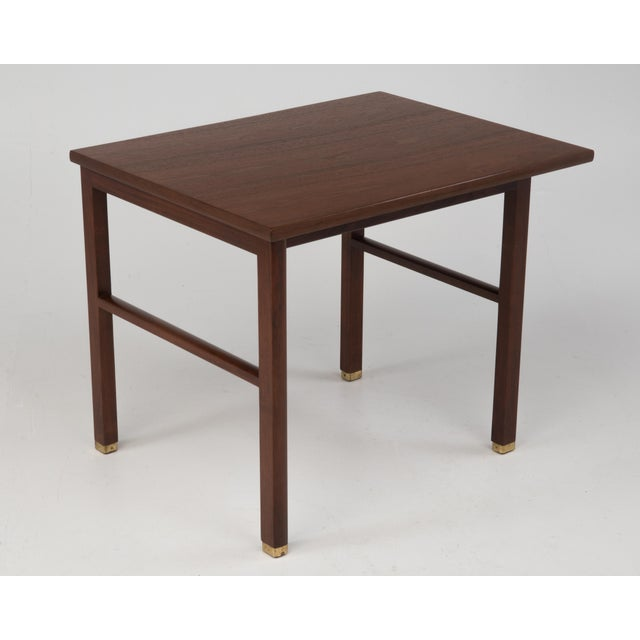 Cantilevered teak end table by Edward Wormley for Dunbar, c. 1960's. Features cantilevered top and brass feet. Retains the...