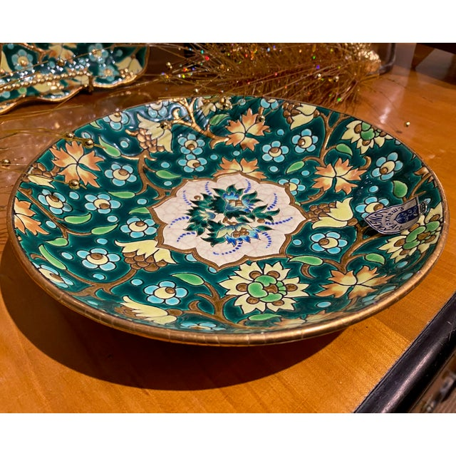 De Longwy plate from France with a blue, yellow and green floral design. Signed on reverse.