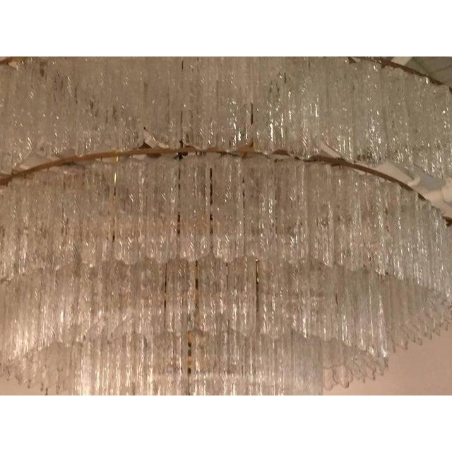 Stunning Elegant Italian Mid-Century Modern Tronchi circular form chandelier comprising a metal frame containing five...