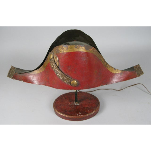 A very charming early 20th century lamp in the form of a tole metal Napoleonic chapeau, mounted on a wood base. Wired to...