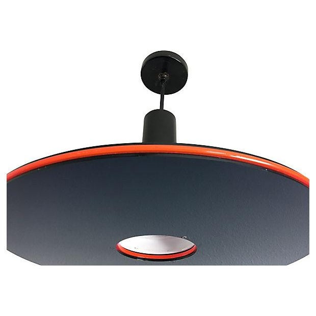 Planetary cool 1970s modern pendant light by F. Ramond comprised of three Lucite discs in black and neon orange/pink...